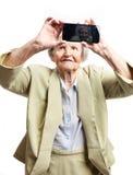 Äldre kvinna som använder mobilen för att ta selfie Arkivfoton