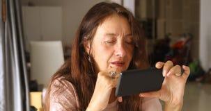 Äldre kvinna som använder smartphonen royaltyfria foton