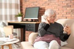 Äldre kvinna som använder smartphonen på soffan royaltyfri bild