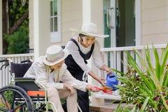 Äldre kvinna som arbeta i trädgården med dottern Arkivbild