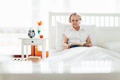 Äldre kvinna som bekvämt sitter i säng som läser hennes favorit- bok royaltyfri fotografi