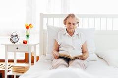 Äldre kvinna som bekvämt sitter i säng som läser hennes favorit- bok Arkivfoto