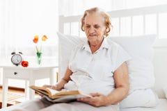 Äldre kvinna som bekvämt sitter i säng som läser hennes favorit- bok royaltyfria bilder