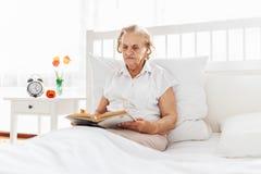 Äldre kvinna som bekvämt sitter i säng som läser hennes favorit- bok royaltyfri bild