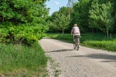 Äldre kvinna som cyklar i Perlacheren Forst royaltyfria bilder