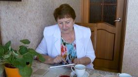 Äldre kvinna som dricker te på tabellen, hållande ögonen på bilder på minnestavlan lager videofilmer