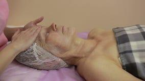Äldre kvinna som får framsidabehandling i skönhetbrunnsort arkivfilmer