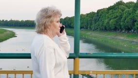 Äldre kvinna som går över bron över floden och talar på smartphonen stock video