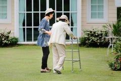 Äldre kvinna som går i trädgård med dottern Arkivfoto