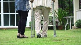 Äldre kvinna som går i trädgård med dottern lager videofilmer