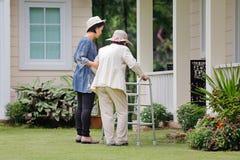 Äldre kvinna som går i trädgård med dottern Arkivfoton