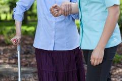 Äldre kvinna som går rymma en sjuksköterska Arkivbilder
