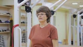 Äldre kvinna som gör sjukgymnastikövningar i konditionrum Sund gymnastik aktiva pensionärer stock video