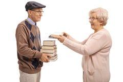 Äldre kvinna som ger böcker till en äldre man Arkivfoton