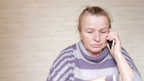 Äldre kvinna som hemma talar på telefonen lager videofilmer