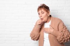 Äldre kvinna som hostar nära tegelstenväggen royaltyfri bild