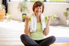 Äldre kvinna som inomhus gör yoga arkivfoto