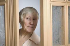Äldre kvinna som kikar till och med dörröppningen Fotografering för Bildbyråer