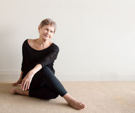 Äldre kvinna som ler göra yoga Royaltyfri Bild