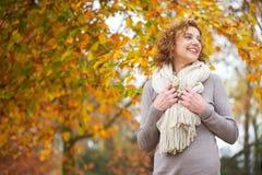 Äldre kvinna som ler i höst Arkivfoton