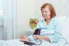 Äldre kvinna som mäter tryck med den digitala sphygmomanometeren, medan sitta i säng Arkivbilder