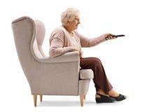 Äldre kvinna som placeras i ändrande kanaler för en fåtölj på TV arkivfoton