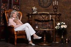 Äldre kvinna som poserar i rum Arkivbilder