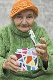 Äldre kvinna som rymmer en gåva Royaltyfri Foto