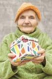 Äldre kvinna som rymmer en gåvaask Royaltyfria Foton