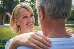 Äldre kvinna som rymmer hennes förälskelse och att se honom i ögat med leende på hennes framsida royaltyfri fotografi