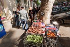 Äldre kvinna som säljer frukter på den smala gatan av den gamla staden Royaltyfria Bilder