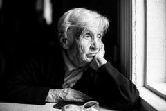 Äldre kvinna som SAD ut ser fönstret arkivfoton