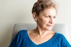 Äldre kvinna som ser eftertänksam Arkivbild