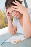 Äldre kvinna som ser ett kvitto för betalning av hjälpmedel Royaltyfri Bild
