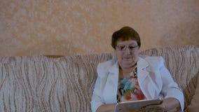 Äldre kvinna som ser foto på din minnestavla arkivfilmer
