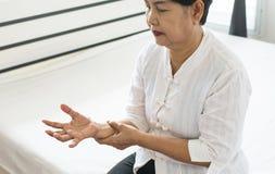 Äldre kvinna som ser hennes hand och lider med parkinsons tecken för sjukdom arkivbilder