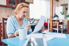 Äldre kvinna som ser hennes nytto- räkningar royaltyfri bild