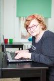 Äldre kvinna som ser kameran och skriver på bärbara datorn Fotografering för Bildbyråer