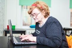 Äldre kvinna som ser slut och skriver på bärbara datorn Fotografering för Bildbyråer