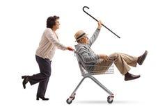 Äldre kvinna som skjuter en shoppingvagn med en hög ridninginsid arkivbilder
