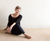 Äldre kvinna som skrattar göra yoga Royaltyfri Bild