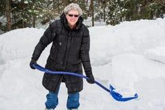 Äldre kvinna som skyfflar snö royaltyfria foton