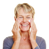 Äldre kvinna som smeker hennes hud royaltyfri foto