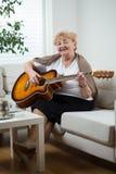 Äldre kvinna som spelar gitarren Royaltyfri Fotografi