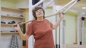 Äldre kvinna som svänger med pinnen som gör sjukgymnastikövningar i konditionrum Sund gymnastik aktiva pensionärer lager videofilmer
