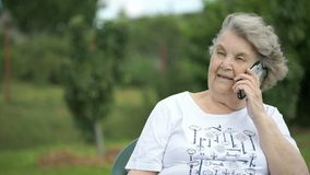 Äldre kvinna som talar genom att använda en smart telefon utomhus arkivfilmer