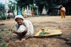äldre kvinna som upp gör ren trädgården av en kloster, medan en munk förbigår i bakgrunden framme av många små stupas fotografering för bildbyråer