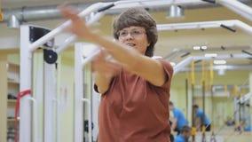 Äldre kvinna som ut sträcker och att göra övningar i konditionrum Sund gymnastik aktiva pensionärer lager videofilmer