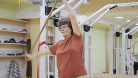 Äldre kvinna som ut sträcker och att göra lutandeövningar med pinnen i konditionrum Sund gymnastik aktiva pensionärer stock video