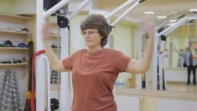 Äldre kvinna som ut sträcker och att göra sjukgymnastikövningar i konditionrum Sund gymnastik aktiva pensionärer arkivfilmer